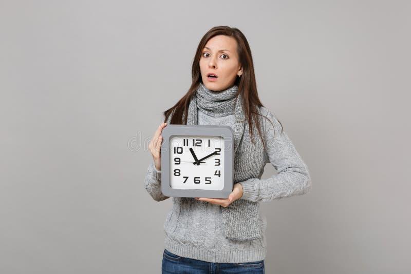 In verwarring gebrachte jonge vrouw in grijze sweater, de vierkante die klok van de sjaalgreep op grijze achtergrond, studioportr stock foto