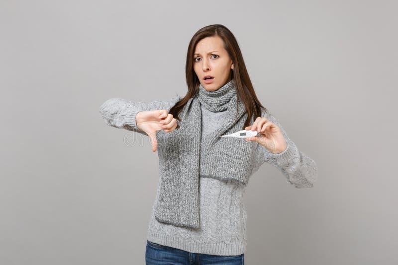 In verwarring gebrachte jonge vrouw in grijze sweatersjaal die duim tonen die neer, greepthermometer op grijze muurachtergrond wo royalty-vrije stock foto