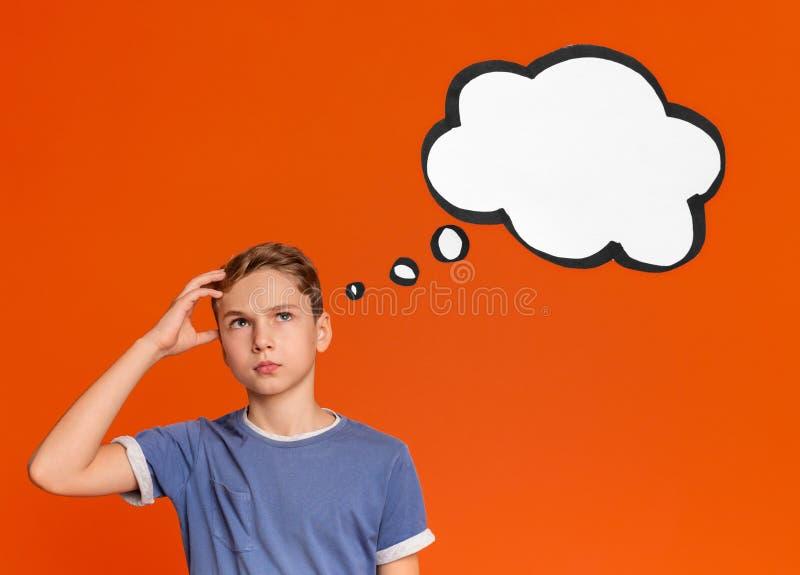 In verwarring gebrachte tienerjongen die zijn hoofd en het denken krassen royalty-vrije stock afbeelding