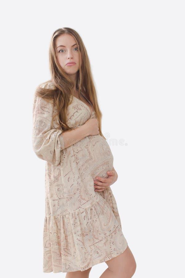 In verwarring gebrachte, verstoorde zwangere vrouw die haar buik houden royalty-vrije stock fotografie