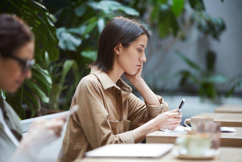 In verwarring gebrachte vrouw die artikel in koffie onderzoeken royalty-vrije stock foto's