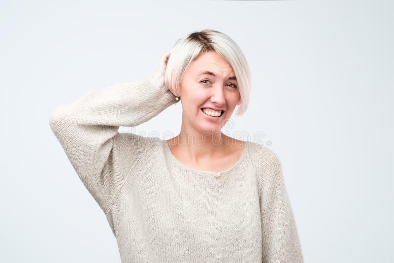In verwarring gebrachte vrouw met geverft kort haar die grijze sweater dragen die camera onderzoeken die sommige twijfels hebben royalty-vrije stock afbeelding