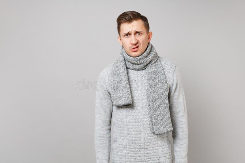 In verwarring gebrachte weerzinwekkende jonge mens in grijze sweater, sjaal status geïsoleerd op grijze muurachtergrond in studio stock foto