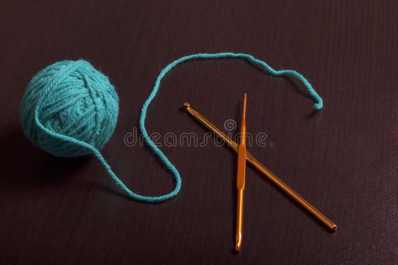 Verwarring van draad voor het breien smaragdgroene kleur en haken voor het breien op een donkere achtergrond royalty-vrije stock afbeelding