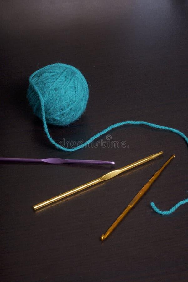 Verwarring van draad voor het breien smaragdgroene kleur en haken voor het breien op een donkere achtergrond stock afbeeldingen