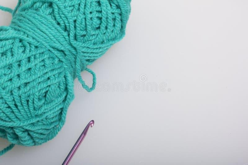 Verwarring van draad voor het breien smaragdgroene kleur en haken voor het breien op een witte achtergrond royalty-vrije stock afbeeldingen
