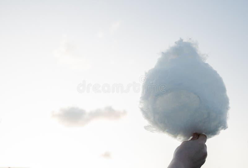 Verwarring van zoete gesponnen suiker zoals een wolk in uw hand tegen de hemel royalty-vrije stock foto