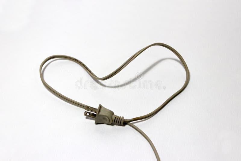 Verwendete Sahnefarbe des Steckers mit Kabel setzte sich wie ein Herz auf den weißen Boden, Liebeskonzept des Elektrikers lizenzfreie stockfotografie