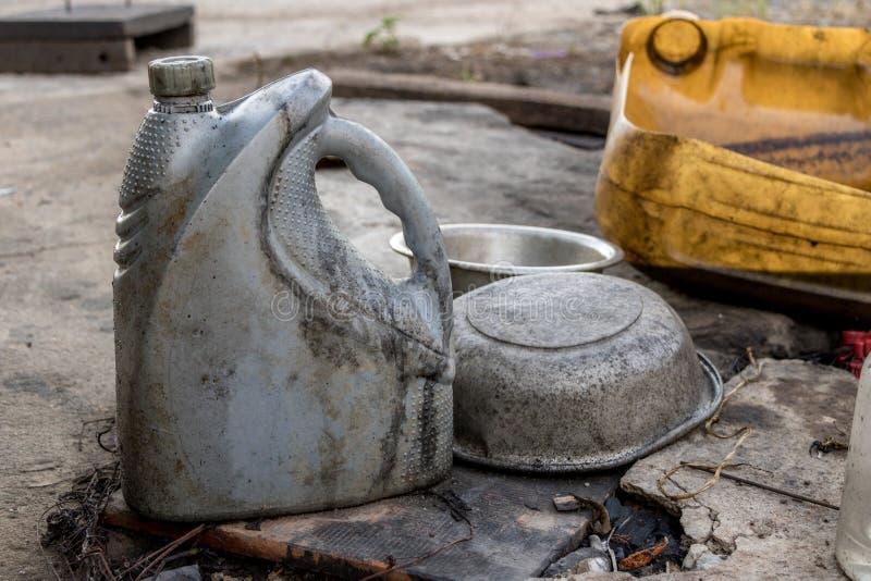 Verwendeter Gray Diesel Oil Bottle ohne Aufkleber - schmutzige schmierige Aluminiumschüssel auf altem konkretem Boden lizenzfreies stockfoto