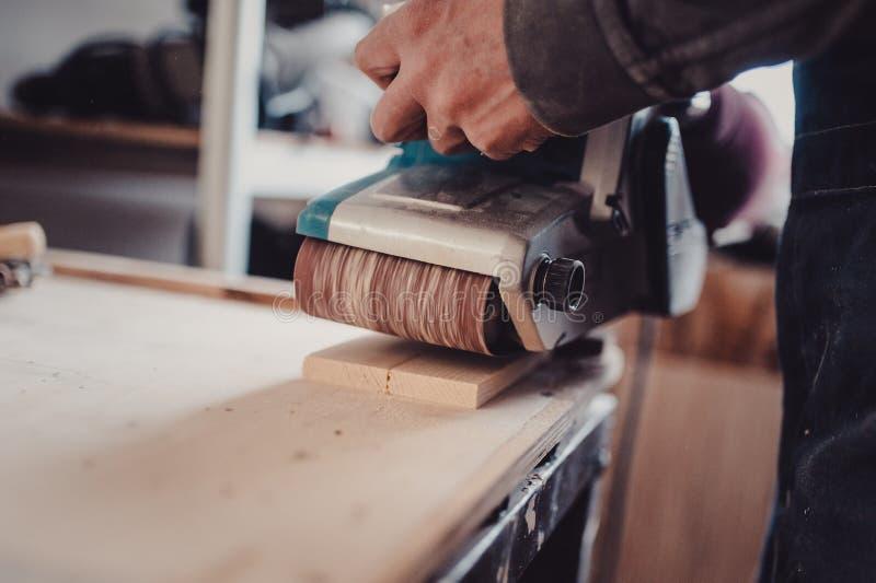 Verwerking van een meubilairdeel door een machine om een boom op te poetsen stock foto
