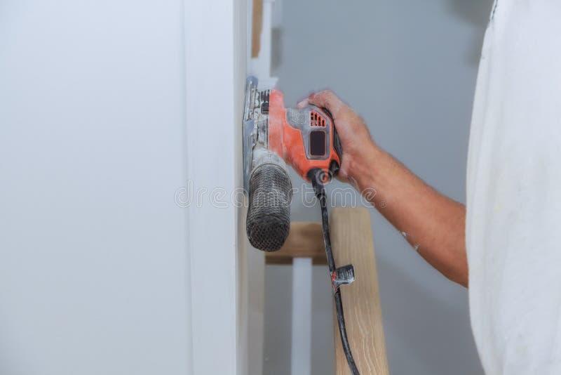 Verwerking van een meubilairdeel door een machine om een boom op te poetsen de malende machine op een raad, stock fotografie