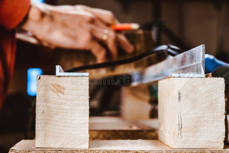 Verwerking van een meubilairdeel door een machine om een boom op te poetsen de malende machine op een raad, selectieve nadruk stock foto's