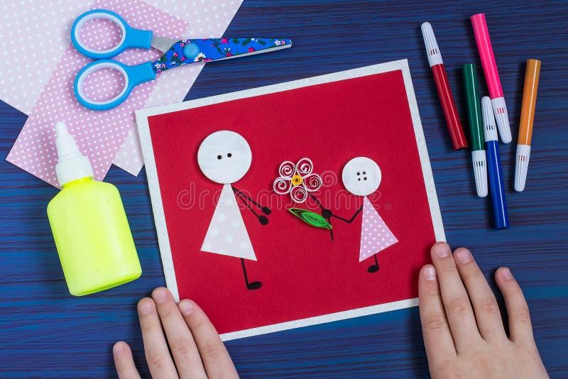 Verwezenlijking een groetkaart voor de Moeder` s Dag door het kind stap royalty-vrije stock foto