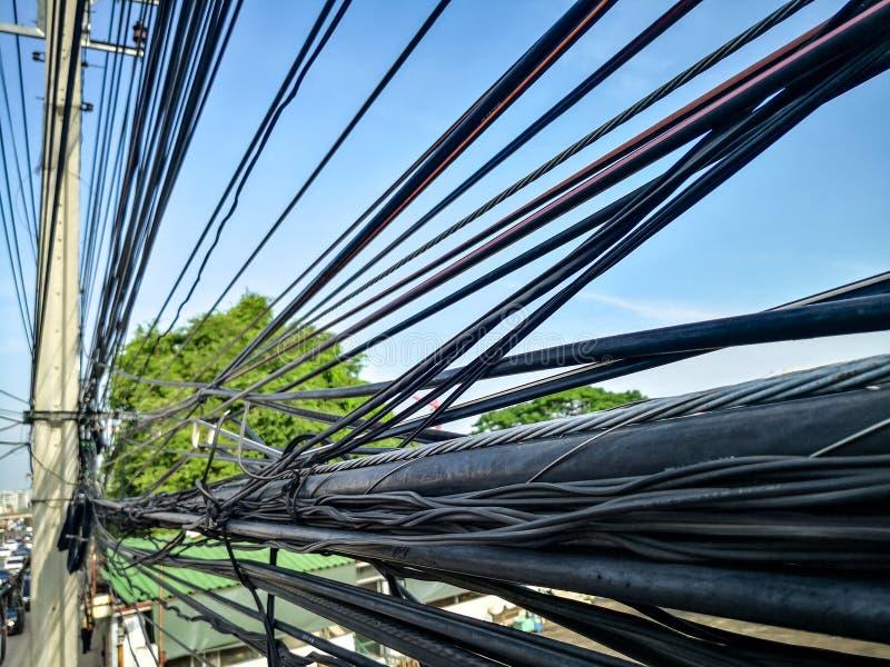Verwicklung von elektrischen Kabeln und von Kommunikationsdrähten auf elektrischem Pfosten stockfotografie