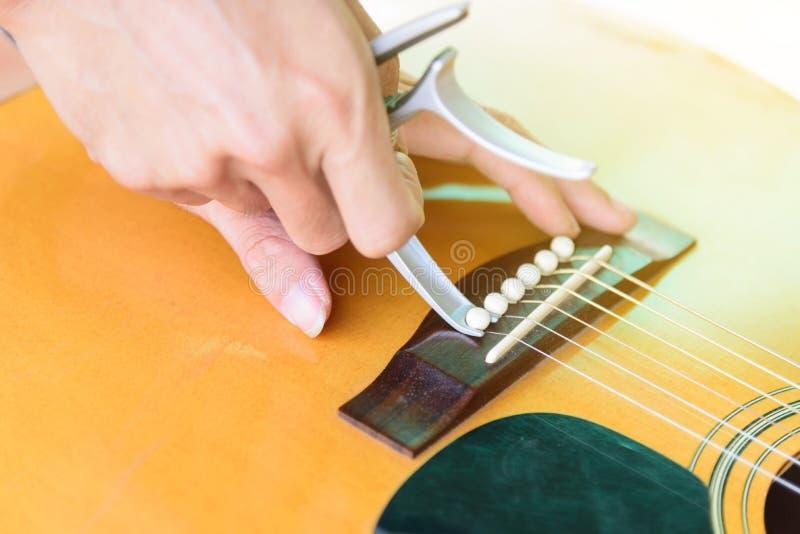 Verwijder de akoestische speld van de gitaarbrug door capo stock fotografie