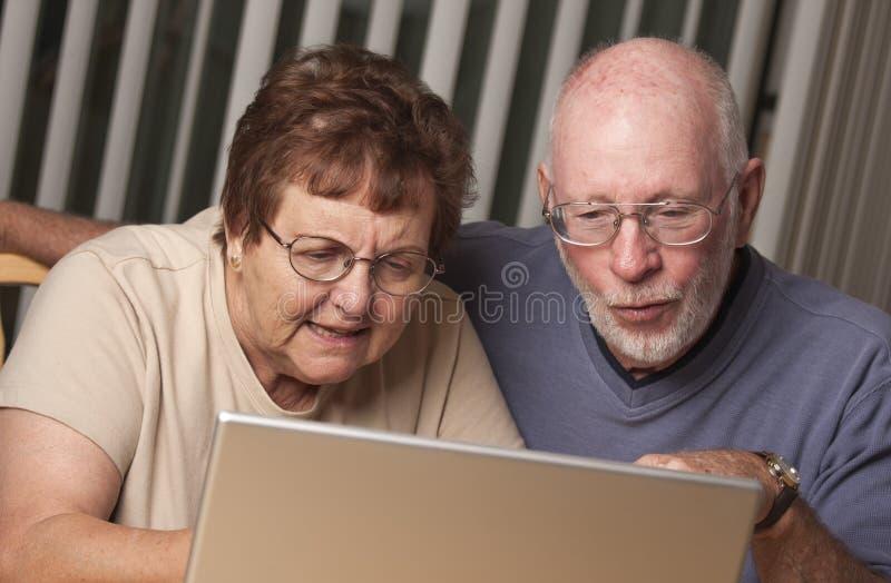 Verwirrte ältere erwachsene Paare, die Spaß auf dem Computer haben stockfotografie