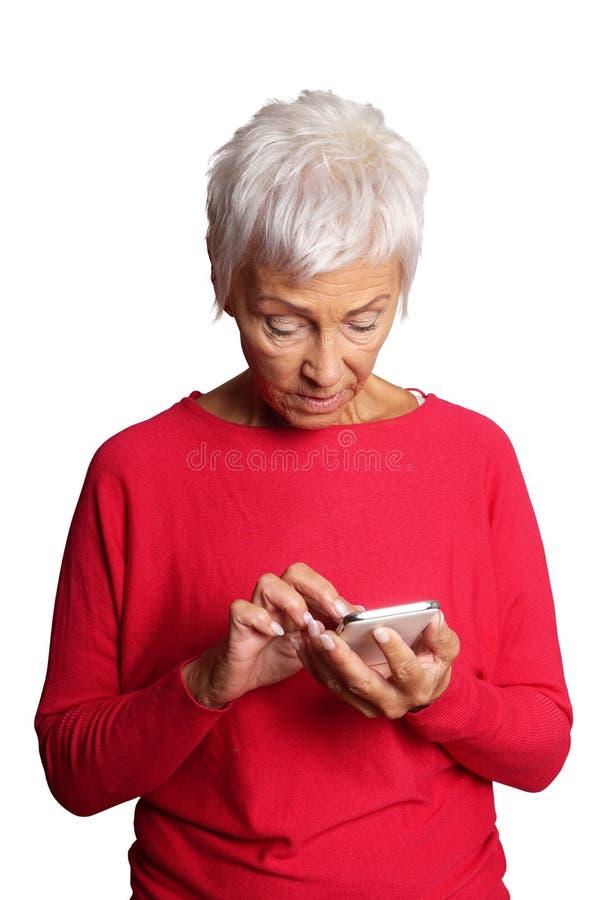 Verwirrte ältere Frau, die Smartphone verwendet stockfoto