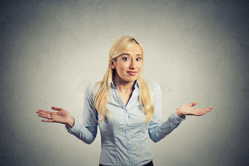 Verwirrte ahnungslose Frau bewaffnet zuckt heraus Schultern lizenzfreies stockbild