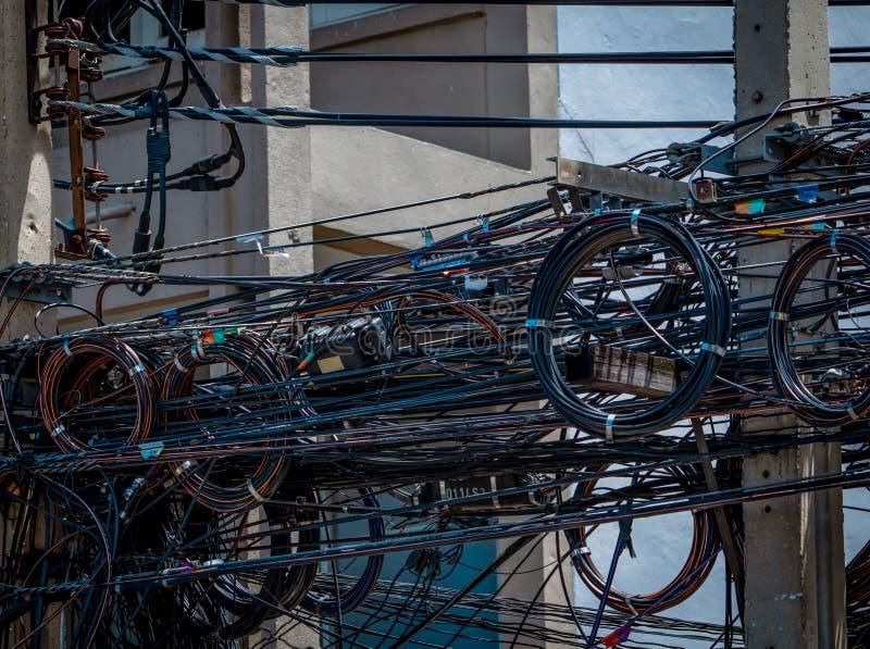 Verwirrte elektrische Dr?hte auf st?dtischem elektrischem Pfosten Durcheinandergebracht und unordentlich zum Organisationsmanagem stockfoto