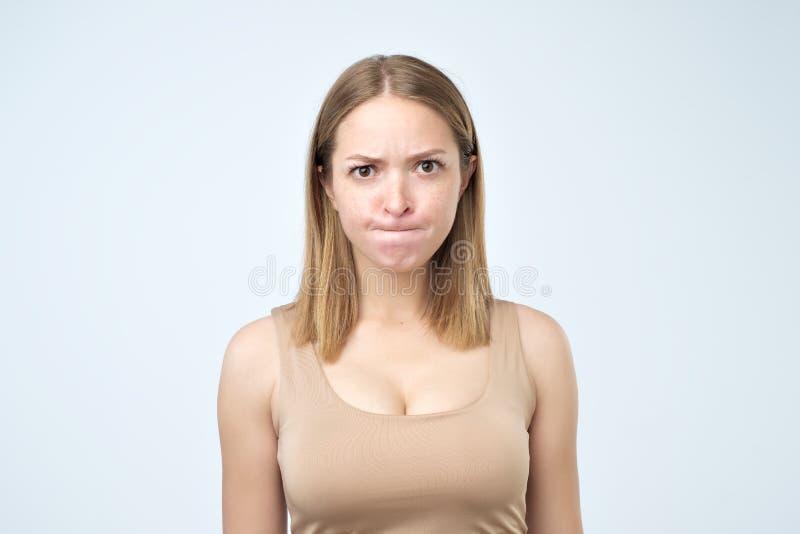 Verwirrte Frau, die mit großen geöffneten Augen die Kamera beißt ihre Lippen und hat etwas Zweifel und Ungewissheit untersucht stockfoto