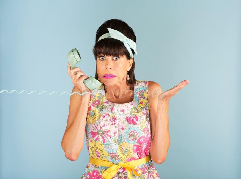 Verwirrte Frau, die Telefon hält lizenzfreie stockfotografie