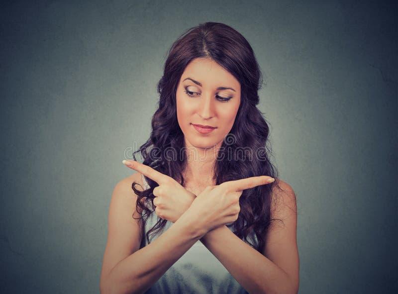 Verwirrte Frau, die in zwei verschiedene Richtungen zeigt stockfoto