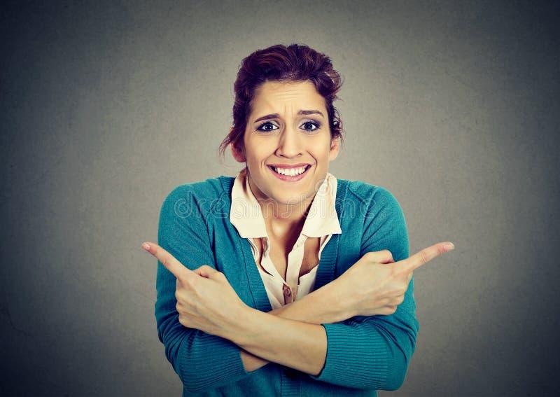 Verwirrte Frau, die in zwei verschiedene Richtungen zeigt lizenzfreies stockfoto