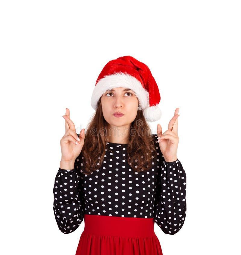 Verwirrte Frau mit dem Anheben von Händen mit den gekreuzten Fingern, Wunsch gewinnen lassend emotionales Mädchen im Weihnachtsma stockfotografie