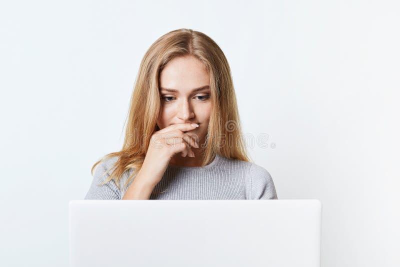 Verwirrte Frau mit schönem Auftritt liest Nachrichten online und fokussiert wird auf Laptop-Computer Junger Student arbeitet an s lizenzfreie stockbilder