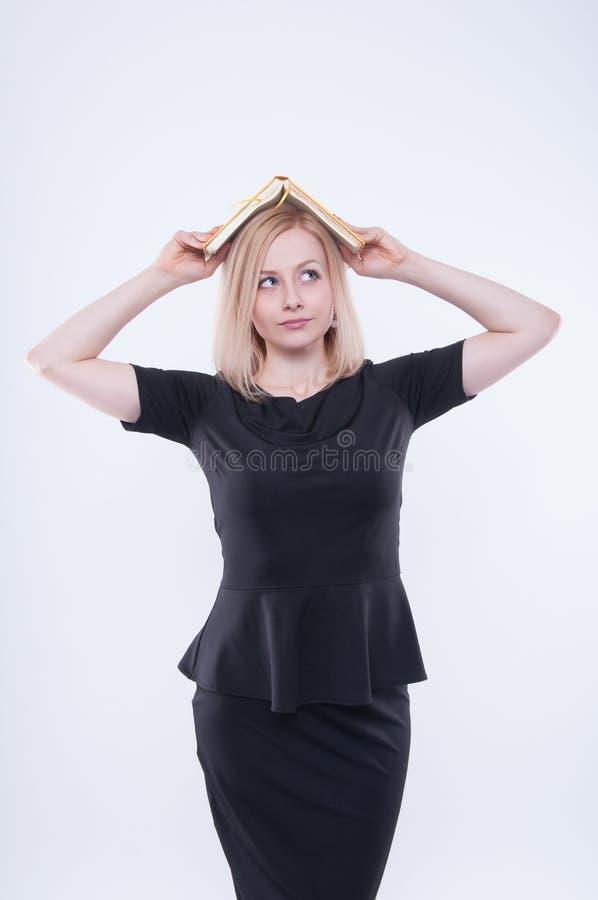 Verwirrte Geschäftsfrau im schwarzen Kleid hält das gelbe Buch auf ihrem Kopf stockbild
