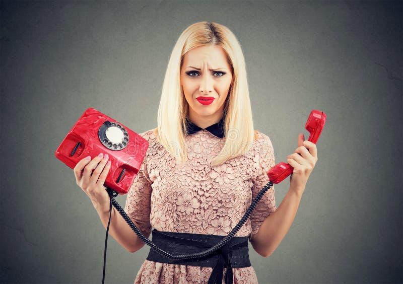 Verwirrte gestörte Frau mit altmodischem Telefon stockfotografie