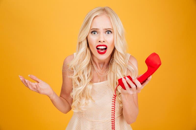 Verwirrte junge Blondine, die Telefon halten lizenzfreie stockbilder
