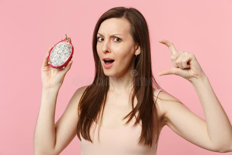 Verwirrte junge Frau, die Größe mit dem Arbeitsplatz demonstrierend, frisches reifes pitahaya halten gestikuliert, Drachefrucht a lizenzfreie stockbilder