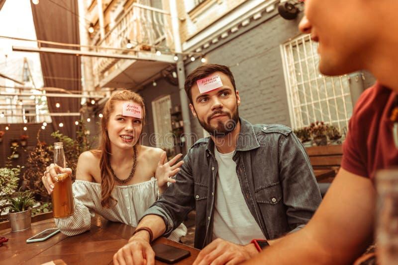 Verwirrte Kameraden, die Zeit an der Stange spielt hedbanz Spiel verbringen stockfotografie