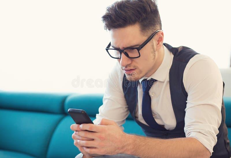 Verwirrte Mannlesemitteilung auf Smartphone stockfotos