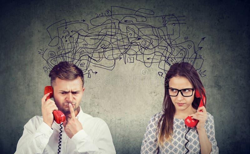 Verwirrte Paarfrau und -mann, die am Telefon austauscht mit vielen negativen Gedanken spricht lizenzfreies stockbild