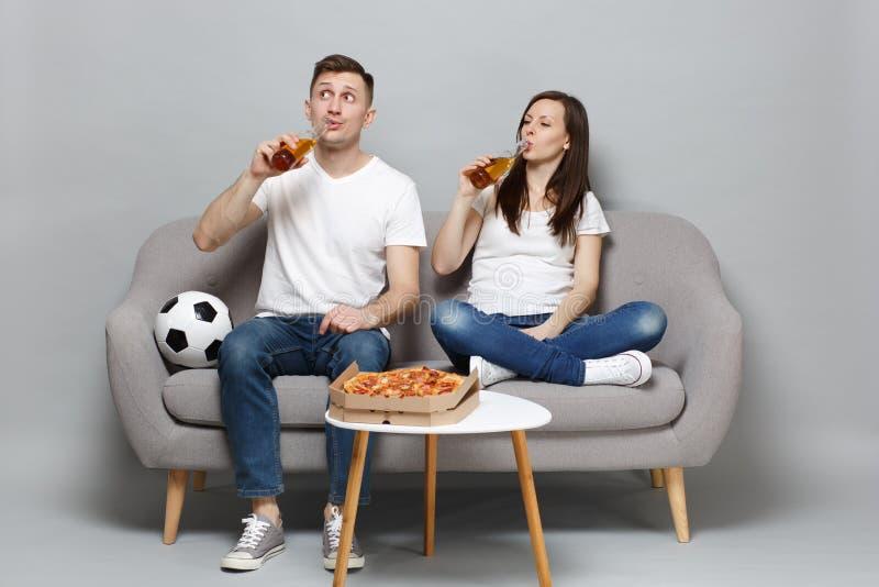 Verwirrte Paarfrauen-Mannfußballfane jubeln oben Stützlieblingsteam mit dem Fußball zu und trinken Bier von den Flaschen stockfotografie