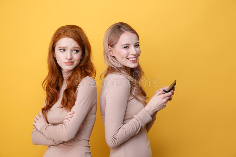 Verwirrte Rothaarigedame nahe dem blonden glücklichen Frauenplaudern lizenzfreie stockfotografie