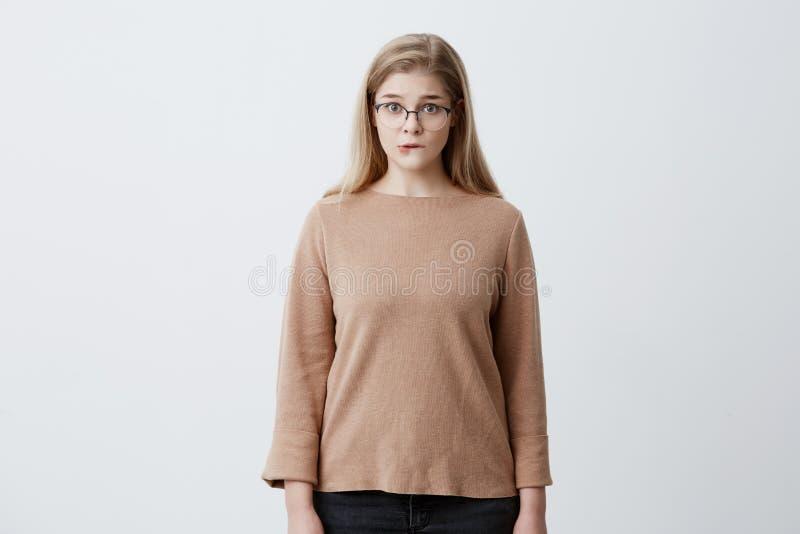 Verwirrte tragende Brillen der hübschen Frau mit dem geraden blonden Haar, das ihre untere Lippe untersucht mit Überraschung Kame lizenzfreie stockfotos