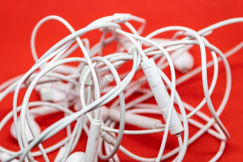 Verwirrte weiße Kopfhörer und Kabel, der Knoten von Kopfhörern lizenzfreie stockbilder