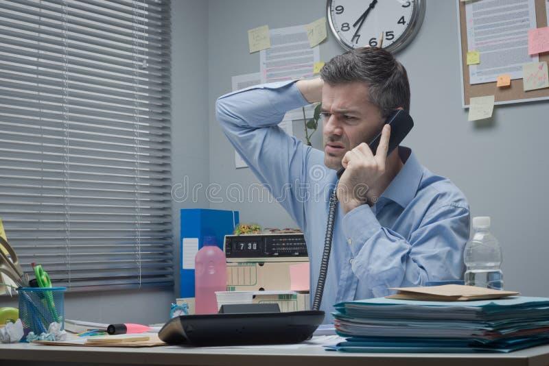 Verwirrter Angestellter am Telefon lizenzfreie stockfotos