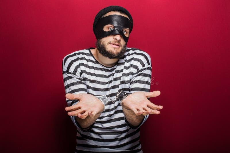 Verwirrter Dieb mit den Handschellen stockfoto