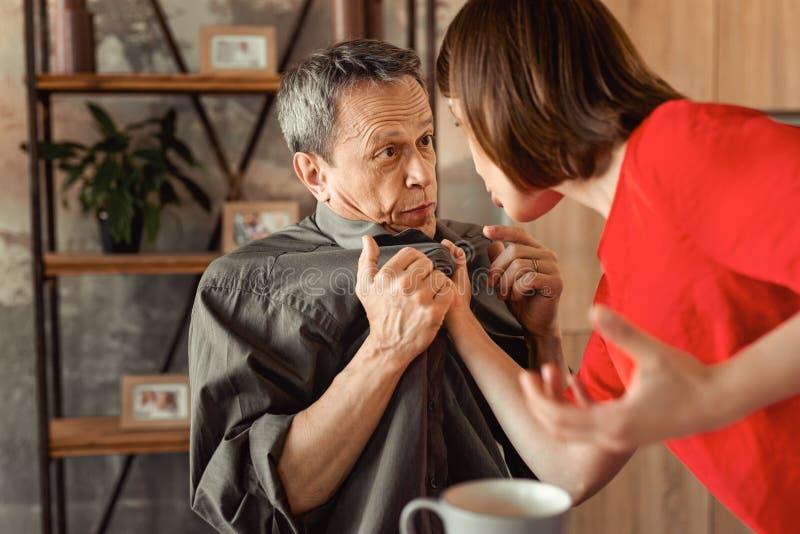 Verwirrter erschrockener Ehemann, der auf seiner Frau während sie schreiend ihm betrachtet stockfoto