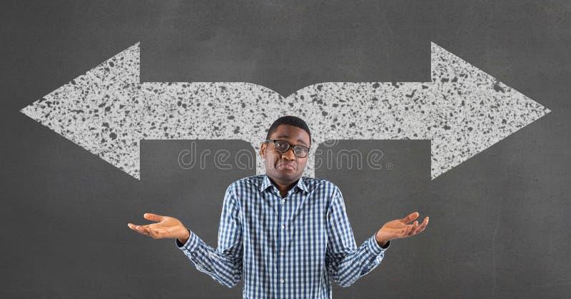 Verwirrter Geschäftsmann, der gegen grauen Hintergrund mit weißen Pfeilen steht lizenzfreie stockfotos