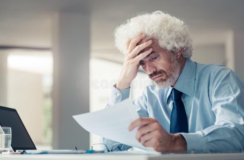 Verwirrter Geschäftsmann, der schlechte Nachrichten empfängt lizenzfreies stockbild