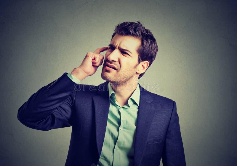 Verwirrter Geschäftsmann, der seinen Kopf verkratzend denkt stockbild
