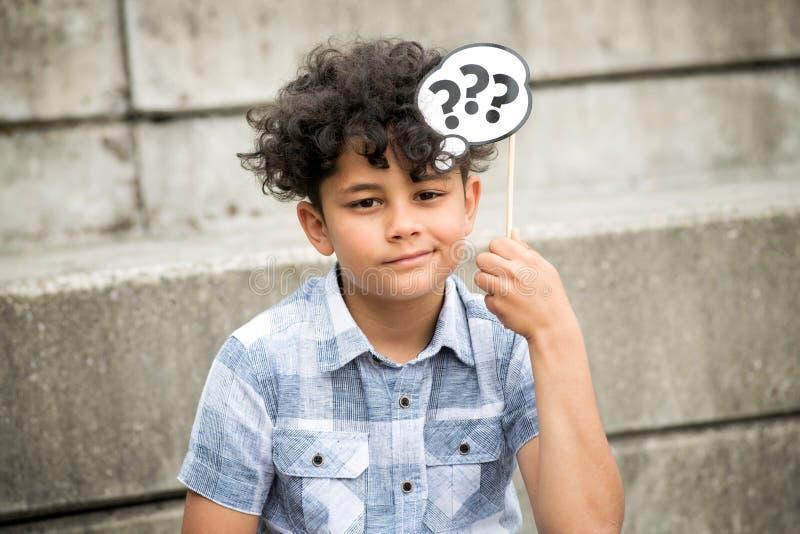 Verwirrter Junge mit Fragezeichen stockfoto