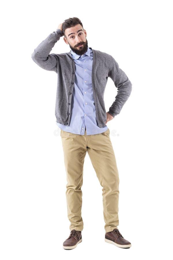 Verwirrter junger bärtiger stilvoller zufälliger Mann mit der Hand im Haar, das Kamera betrachtet lizenzfreies stockfoto