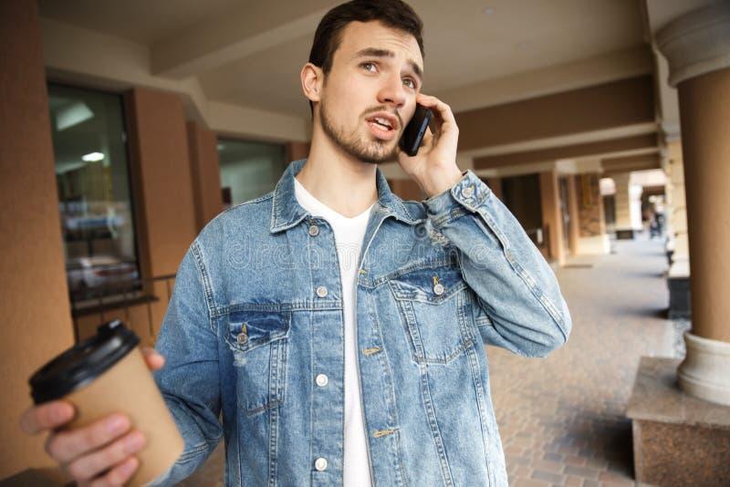 Verwirrter junger Kerl spricht am Telefon beim Halten einer Papierschale in seiner rechten Hand Er steht auf der Straße lizenzfreie stockbilder