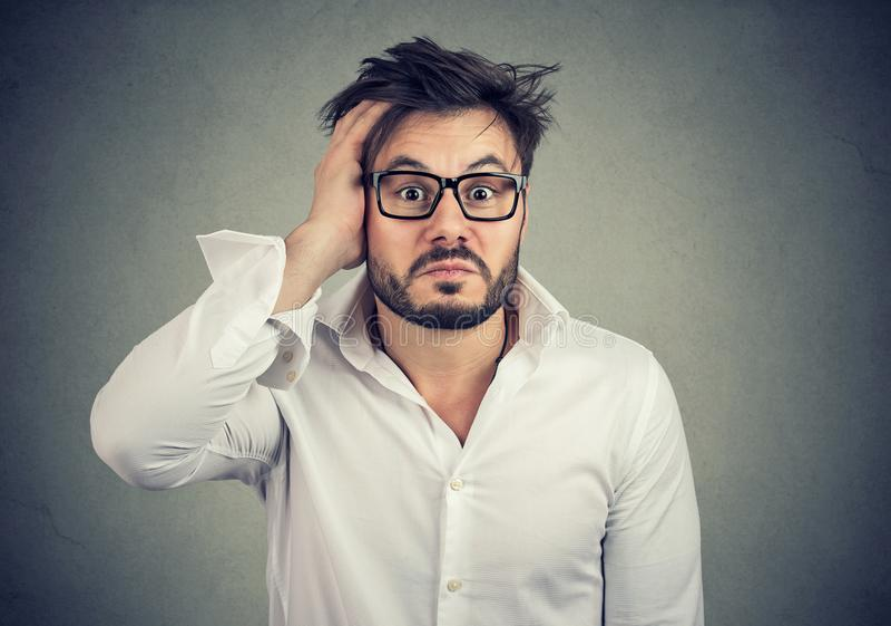 Verwirrter junger Mann, der Hand auf Kopf hält lizenzfreie stockfotos